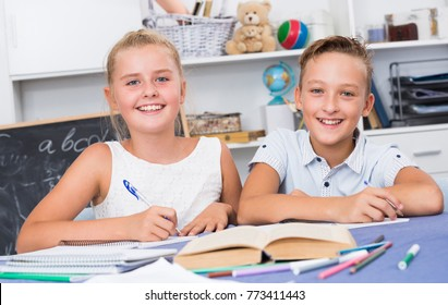 Portrait of brother with sister who are doing homework at home.
