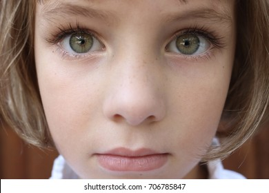 Portrait of a brown haired girl with big green eyes
