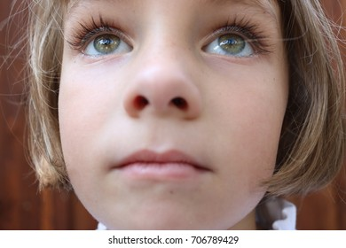 Portrait of a brown haired girl with green eyes looking up in wonder