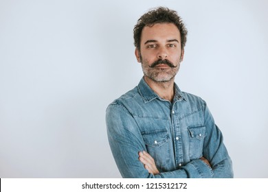 Portrait of brown, handsome man with mustache in jeans shirt standing with crossed arms. Gray background. Copy space