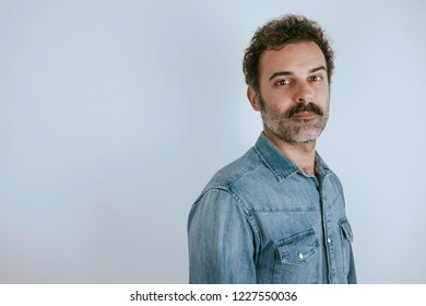 Portrait of brown, handsome man with mustache in jeans shirt standing looking at camera. Gray background.