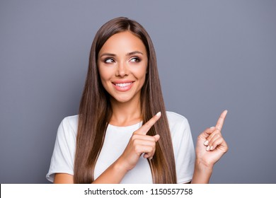 Portrait of brown-haired gorgeous attractive nice smiling young lady with logn hair over grey background, showing pointing up and side with fingers, isolated, copy space