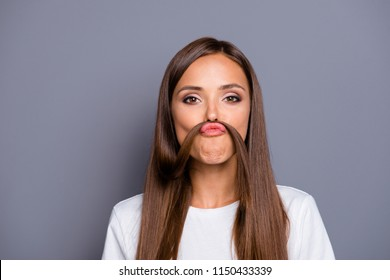 Portrait of brown-haired gorgeous nice young lady grimacing with curl, fake mustache over grey background, isolated