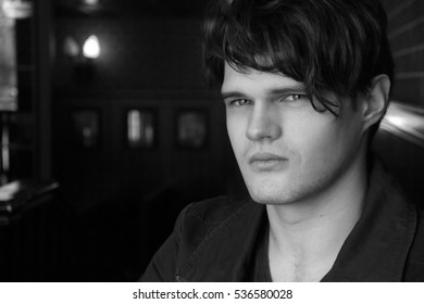 Portrait of brunet guy in black jacket in a dark room of the restaurant, cafe. Dark hair, close-up. Serious look. He looks at the camera. Man calm state. Black and white photo
