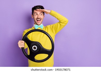 Portrait of brunet impressed guy hold wheel look far wear yellow sweater isolated on pastel lilac color background - Shutterstock ID 1903178071