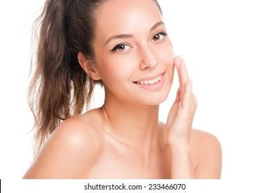 Portrait of a brunette beauty applying moisturizer on her skin.