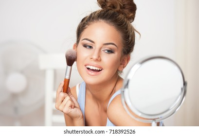 Portrait of brunette beauty doing her makeup in front of a mirror.