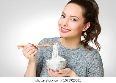 Portrait of a brunette beauty eating asian food.