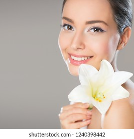 Portrait of brunette beauty in light makeup with white lily flower