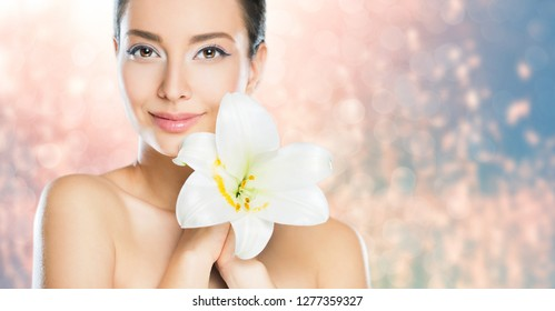 Portrait of brunette beauty in light makeup with white flower.