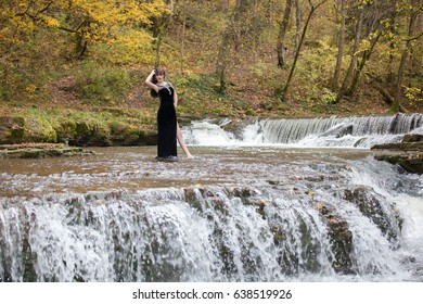 Portrait of a brunette in a black dress near a mountain river. The model is posing at the waterfall.