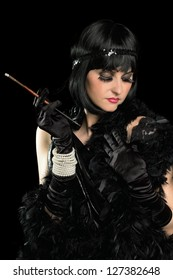 Portrait of brunette with a cigarette holder dressed in retro style. Isolated