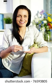 Portrait of brunette with cup of tea sitting on sofa and looking at camera