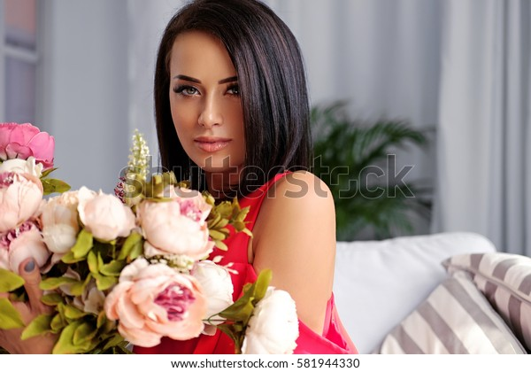 Portrait of brunette female posing with the colorful flower bouquet.