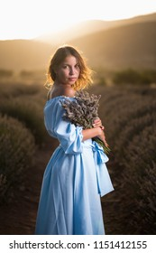Portrait of a brunette girl with a bouquet of lavender in blue dress during sunset