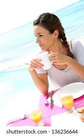 Portrait of brunette girl having coffee by the beach