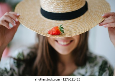 Portrait of brunette girl holding straw panama hat with strawberry on it against white wall background. Face blurred. Close focus on strawberry. She brings it closer to camera.