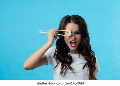 Portrait of a brunette girl who has hadi sushi in her hands. The girl opened her mouth wide in surprise. She brought sushi to her eye