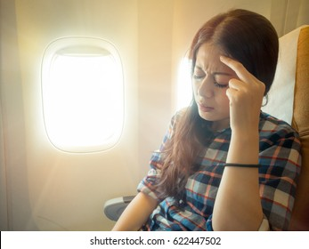 portrait of brunette hair woman headache facial expression on a chair. fear of flying student in plane with pain airsickness with vintage retro film color.