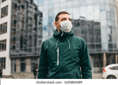 portrait of brunette man in a surgical bandage on a background of a modern building, coronavirus, illness, infection, quarantine, medical mask - Shutterstock ID 1650865489