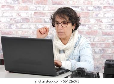 Portrait of brunette mature woman using laptop