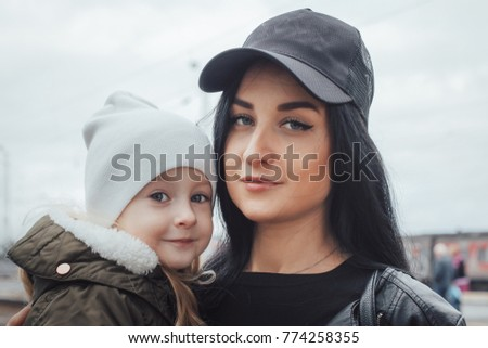 Portrait Of A Brunette Mom In A Cap And Little Girl In A White Hat Outdoors