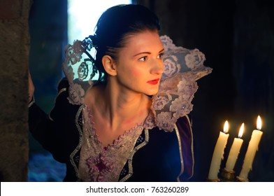 Portrait. Brunette in an old dress with a high white lace collar. In his hand holds a candlestick with three candles. She peeks around the corner