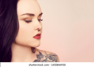 Portrait of a brunette with a pierced nose. Beautiful duvushka with a professional make-up. Woman with piercing in the nose at the bottom, an informal girl. Girl with tattoo and long hair