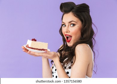 Portrait of brunette pin-up woman 20s in vintage polka dot dress smiling while holding and eating sweet cheesecake isolated over violet background