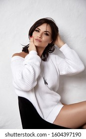 Portrait of brunette sexy beautiful woman shoulder wear cozy knitted white color sweater pretty face skin care tan make up closeup lashes home style fashion dress casual style.