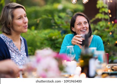 Portrait of a brunette sits with her friends gathered around a table in the garden one summer evening to share a meal and have fun together.
