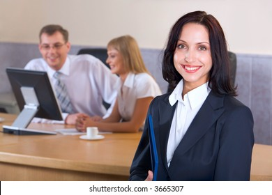 Portrait of brunette smiling businesswoman staring at camera holding blue paper case in her hands and two businesspeople on the background looking at the monitor