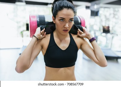 Portrait of brunette sporty woman working out with sandbag while exercise for butt legs in fitness club or gym. Attractive athletic female doing hard workout with weight training with copy space.