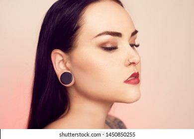 Portrait of a brunette with a tunnel in her ears, and a pierced nose. Beautiful duvushka with a professional make-up. Woman with piercing in the nose, informal girl. Earrings in the nose, jewelry.