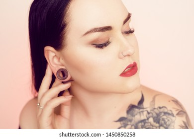 Portrait of a brunette with a tunnel in her ears, and a pierced nose. Beautiful duvushka with a professional make-up. Woman with piercing in the nose, informal girl. Girl with tattoo