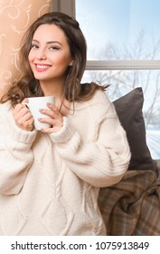Portrait of  a brunette winter beauty having hot beverage.