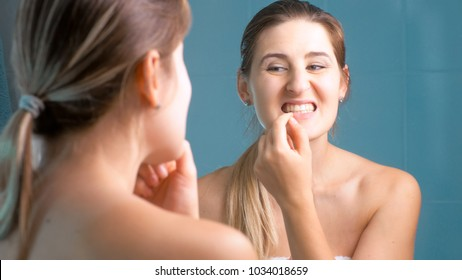 Portrait of brunette woman checking her teeth in bathroom at mirror