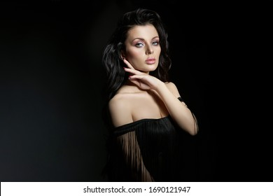 Portrait of a brunette woman with a chic, lush wavy hair, plump lips. Natural cosmetics and beautiful bright makeup on the face of the girl