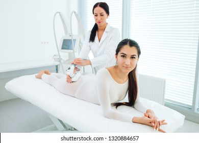 Portrait of brunette woman dressed in white LPG slimming bodysuit, looking at camera while getting lpg integral massage, which is carried out by the latest generation of devices - lpg integral.
