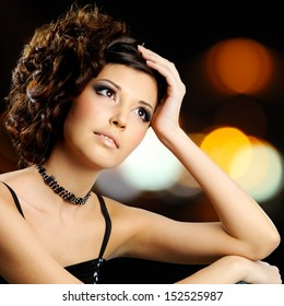 Portrait of brunette woman with fashion hairstyle over night lights bokeh background