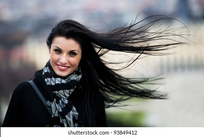 Portrait of a brunette woman - hair blowing in the wind