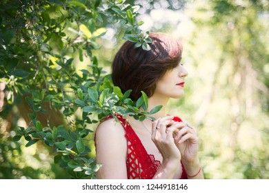 Portrait of a brunette woman with a haircut in profile on nature near a tree