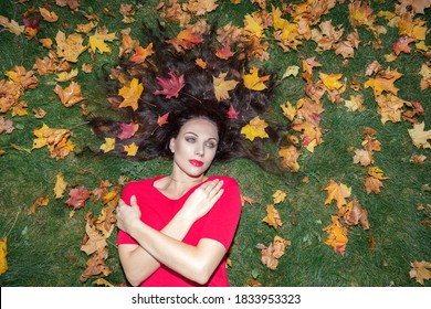 Portrait of a brunette woman with long hair. She lies on green grass in a red dress and maple leaves in her hair. Autumn concept ..