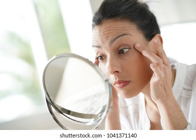 Portrait of brunette woman looking at her face in mirror