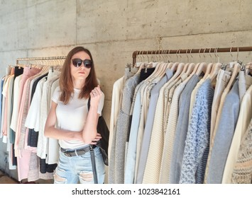 Portrait of brunette woman in sunglasses standing at clothes racks in boutique.