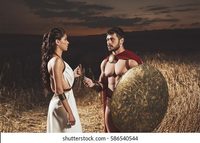 Portrait of brunette woman wearing like greece in white dress giving amulet to man with bread, warrior wearing like spartan. Couple meeting after war at night time.