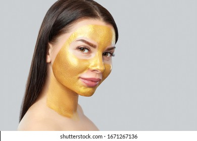 Portrait of a brunette woman who makes a golden mask on her face, neck and collarbones against aging, sagging skin and skin care.Cosmetology concept.