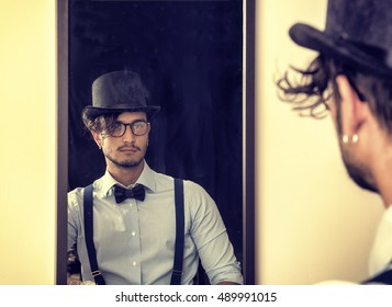 Portrait of brunette young man in glasses, hat, bow-tie, suspenders and shirt looking at himself in a mirror. Vintage look