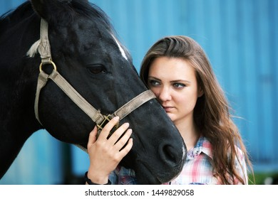 portrait of brunette young woman with her black horse