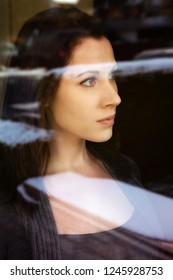 portrait of brunette young woman looking through a window